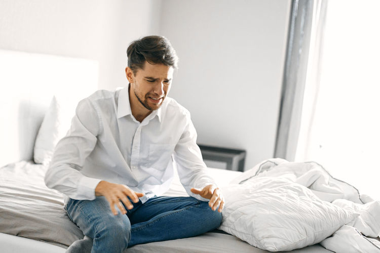 Young man sitting on bed at home