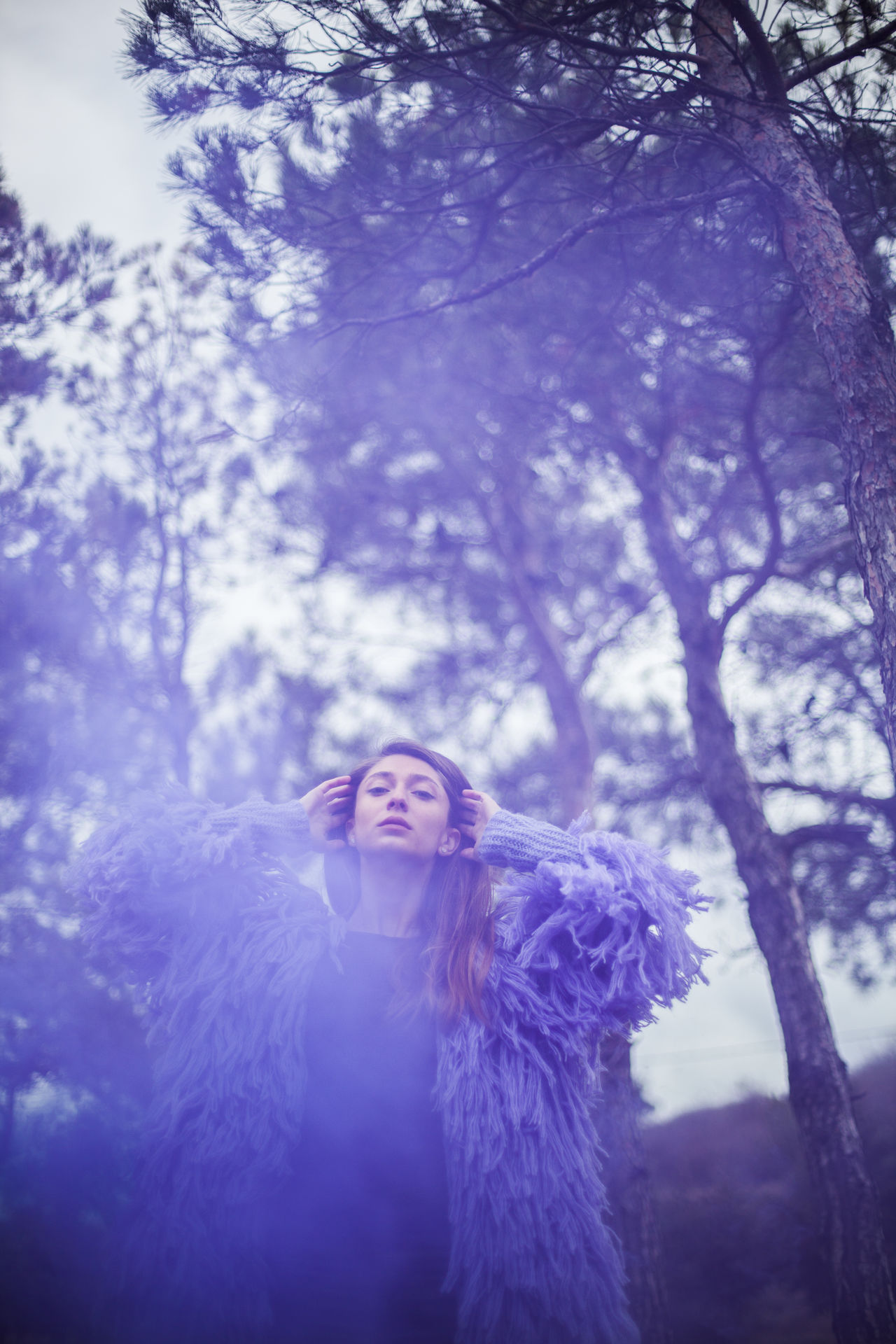 Portrait of woman standing amidst purple smoke against trees