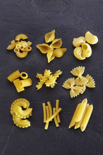 Variety of types and shapes of Italian pasta Black Background Choice Dried Food Food And Drink Freshness Spaghetti Assortment Carbohydrate - Food Type Directly Above Food Freshness Healthy Eating High Angle View Italian Food Large Group Of Objects Macaroni No People Pasta Raw Food Slate Still Life Studio Shot Variation Variety Yellow