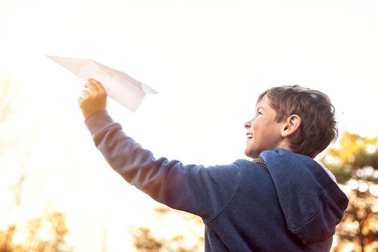 Boy holding umbrella against sky