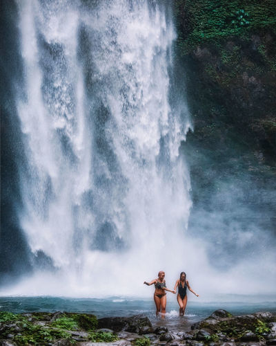 Friends wearing bikini walking against waterfall