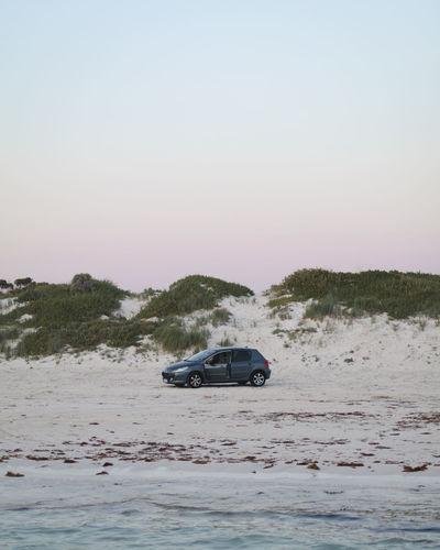 Car on sea shore against clear sky
