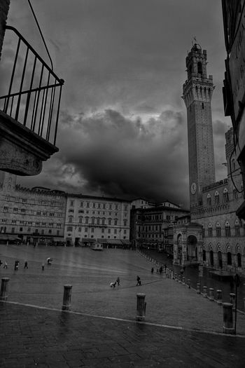 High angle view of palazzo pubblico and torre del mangia against storm clouds