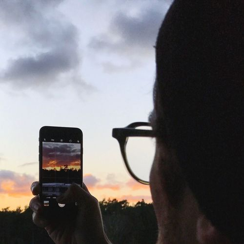 Rear view of man photographing through smart phone against sky