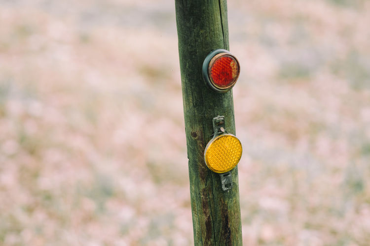 Close-up of road reflectors on wooden post