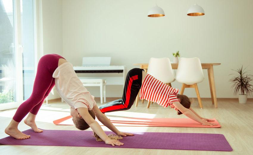 Siblings practicing yoga at home