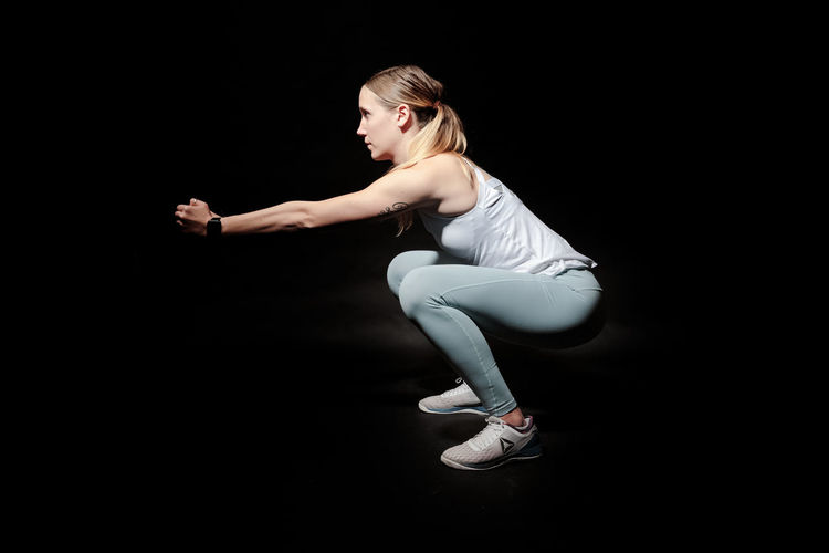 Young woman doing gym excercise against black background Adult Sport Activity Athletic Attractive Beautiful Body Exercise Female Fit Fitness Girl Gym Health Healthy Lifestyle Muscle One person Pilates Pose Slim Sportswear Studio Training Weight Wellness Woman Workout Young Black Background Full Length Studio Shot One Person Indoors  Dancing Young Adult Young Women Side View Sports Clothing Cut Out Lifestyles Clothing Healthy Lifestyle Flexibility Ballet Skill  Hairstyle Beautiful Woman Profile View Effort