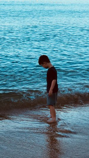 Full Length Side View Of Boy Standing On Sea Shore