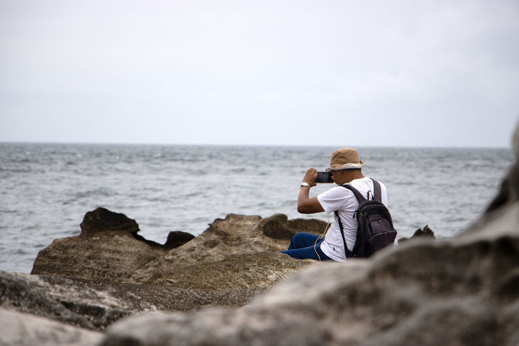 Rear view of man photographing by sea against sky