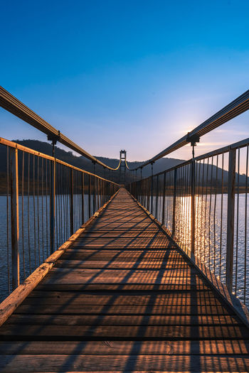 The longest suspension bridge in Bulgaria over Studen Kladenez dam with distance between the two towers of 260m. The only way to reach Lisicite village Reflection Water Sunset Nature Sky Bridge Travel Tower Lake Mountain Direction Pylon Way Suspension Dam Bulgaria Metal Overcast Wooden Suspension Bridge Longest Warm Clothing Built Structure Connection Architecture Bridge - Man Made Structure The Way Forward Diminishing Perspective Railing Transportation No People Footbridge Sunlight Day vanishing point Outdoors Long