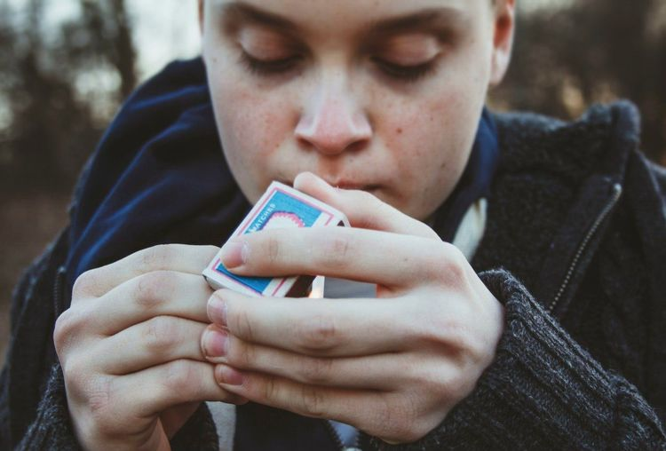 Close-up of a teenage boy lighting cigarette