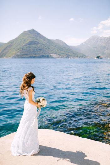 Full length of bride standing against lake