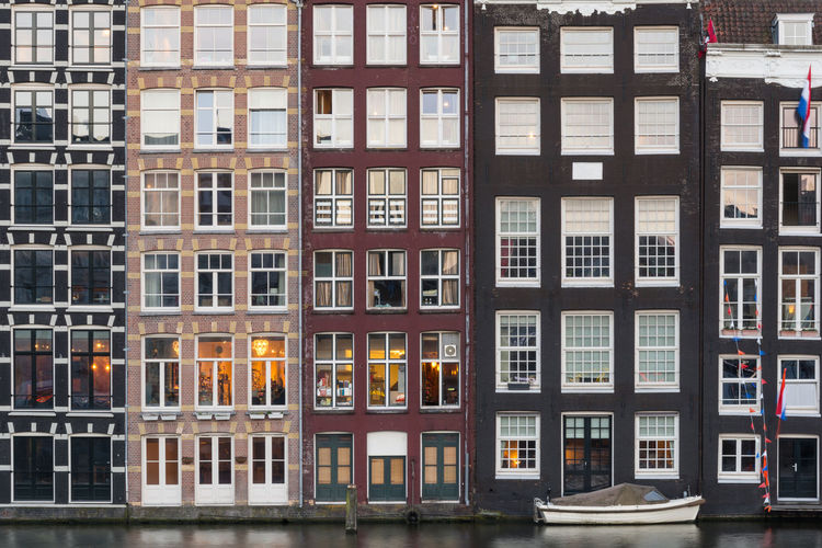 Facades of traditional colorful Dutch houses in Amsterdam, Holland Damrak Amstel Holland Façade Pattern Canal House Colorful Window Traditional Boat Waterfall Architecture Exterior Dutch Travel Capital City Cityscape Apartment Real Estate Illuminated Urban Residential  Backgrounds