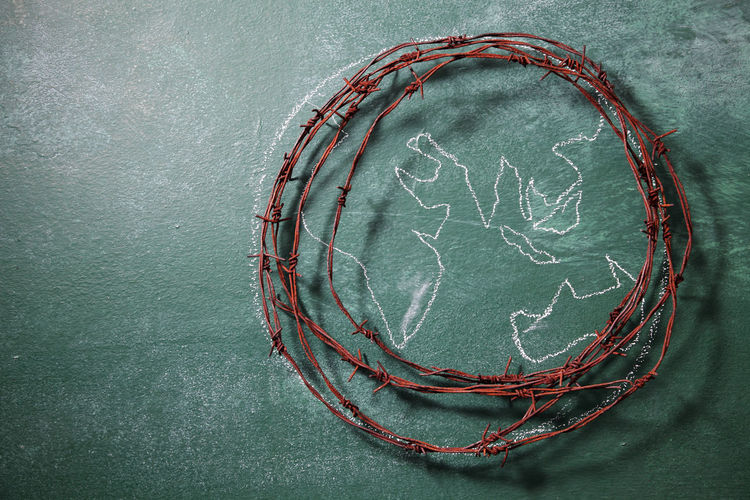 High angle view of rusty barbed wire with globe drawing on blackboard