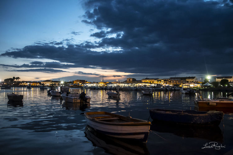 Boats moored in harbor at dusk