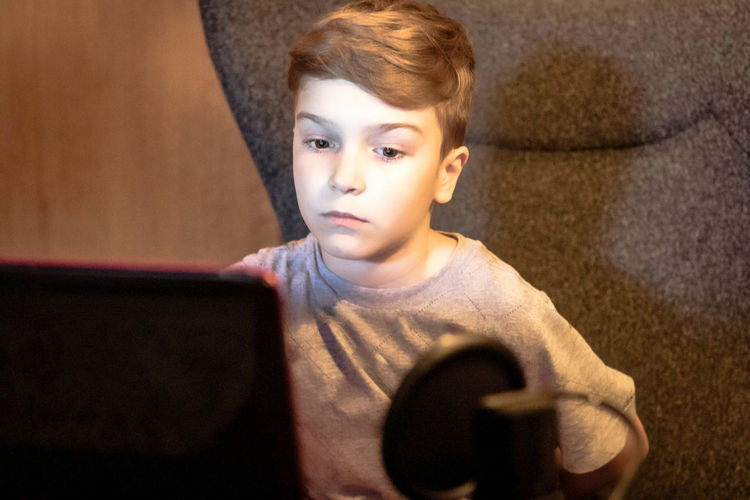 Portrait of boy sitting at home