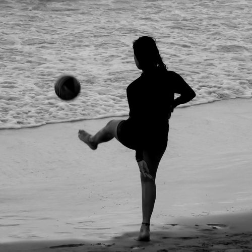 The young black player. World Cup 2018 Beach Beauty In Nature Black & White Black And White Blackandwhite Enjoyment Full Length Hobbies Holding Leisure Activity Nature Non-urban Scene Riverbank Sand Sea Shore Standing Tourism Tourist Tranquil Scene Tranquility Vacations Black And White Friday Weekend Activities Monochrome Photography