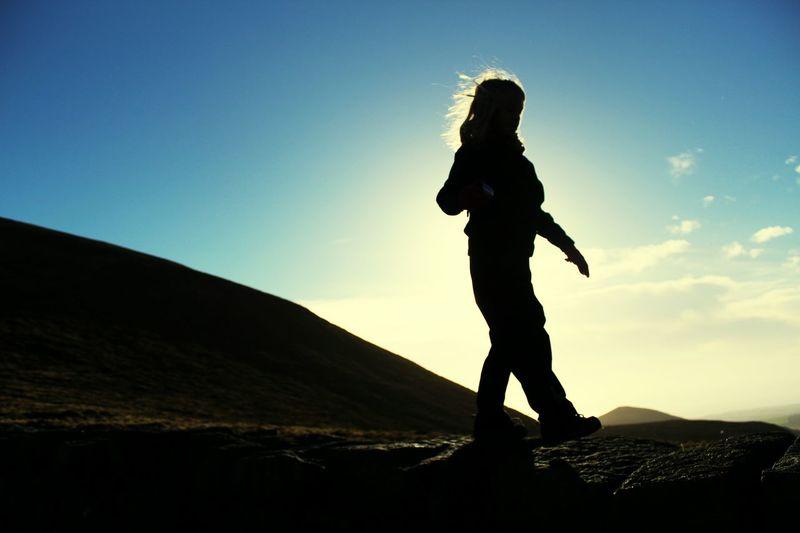 Silhouette girl walking on field by mountain against sky
