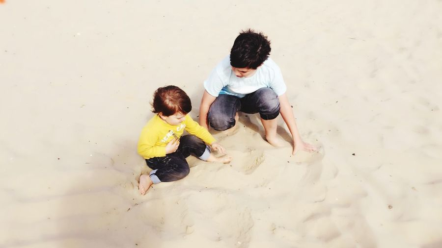 High angle view of brothers playing with sand at beach