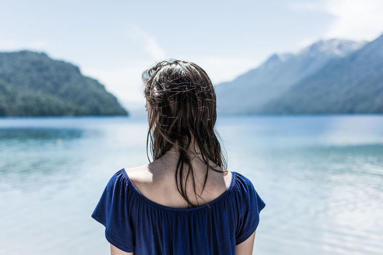 Rear view of young woman standing by lake