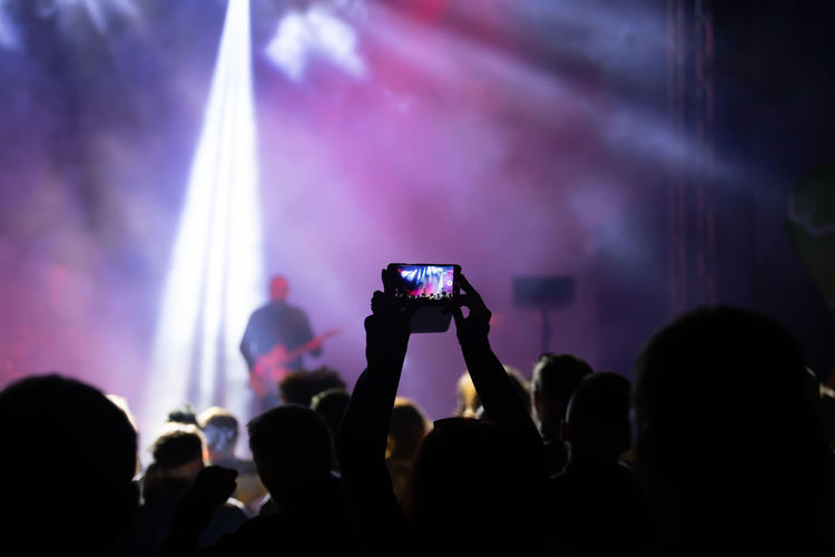 People photographing at music concert