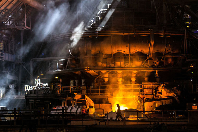 Blast-furnace Metallurgist Person In The Frame Silhouette THE LIGHTS OF A SUN Man Working Architecture Built Structure Burning Factory Fire Fire - Natural Phenomenon Glowing Heat - Temperature Illuminated Indoors  Industry Metal Metal Industry Metallurgical Production Motion Orange Color Production Line Smoke - Physical Structure