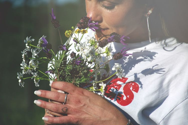 Close-up of woman holding red flowering plant