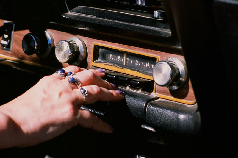 Cropped hand of woman playing music in car