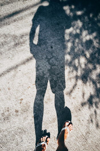 Low Section Of Man Standing On Footpath With Shadow