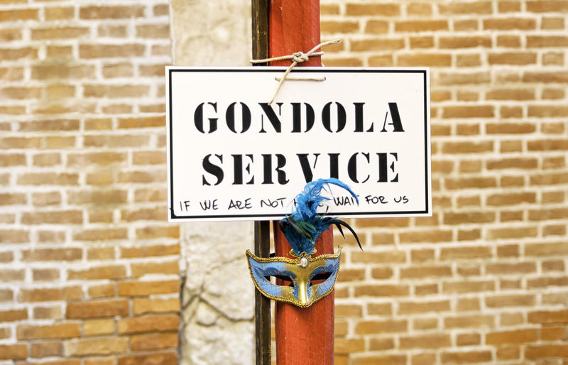 Detail of a Gondola service sign over a red pole in the Venice lagoon. The Gondola s a traditional, flat-bottomed Venetian rowing boat, similar to a canoe Gondola Icon Orange Romantic Service Sign Venetian Wall Writing Boat Bricks Canal Historical Information Italian Italy Message Notice Pole Site Streetsign Symbol Traditional Urban Venice