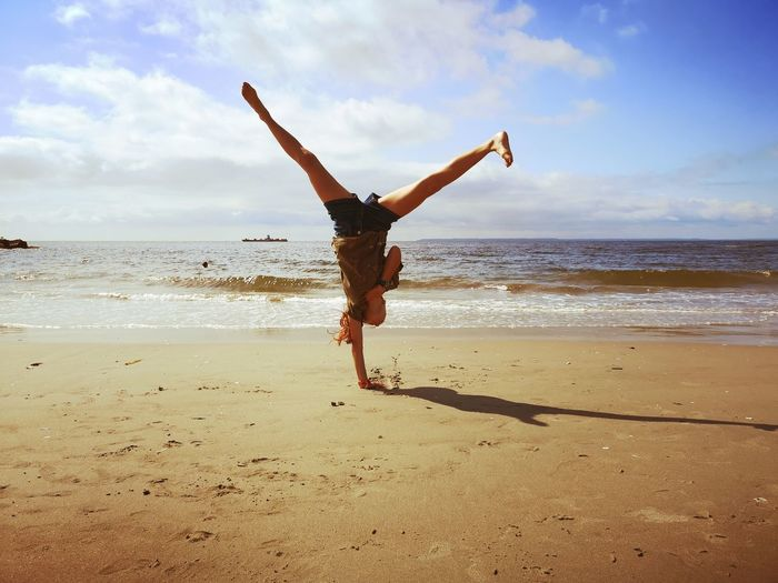 Full length of woman practicing handstand at beach against sky