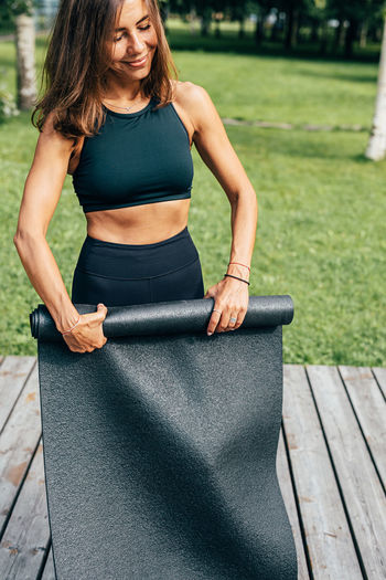 Woman rolling exercise mat while standing outdoors