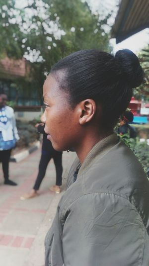 Side View Of Young Woman Looking Away While Standing On Street