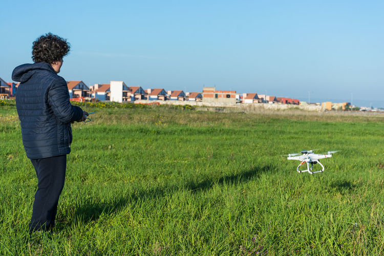 Boy Flying Drone On Grassy Field