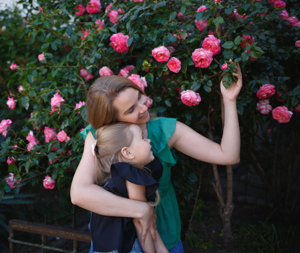 Mother and daughter touching flowers outdoors