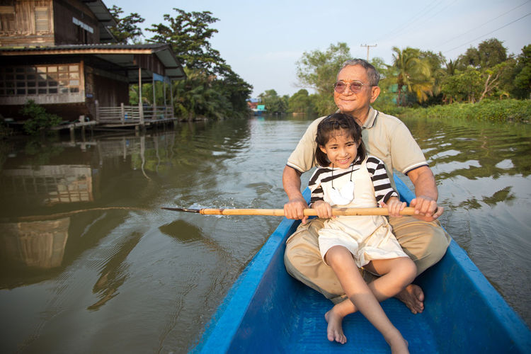 Senior old asian man roll boat with kids in the river in family activity concept