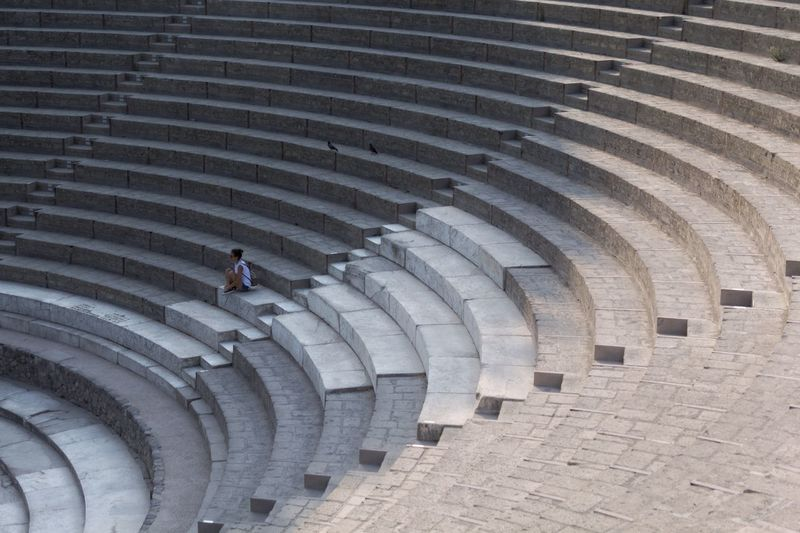 High angle view of woman sitting on staircase at amphitheater