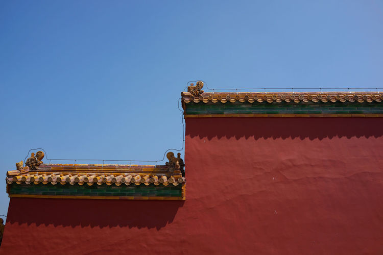 Low angle view of architectural wall against clear sky