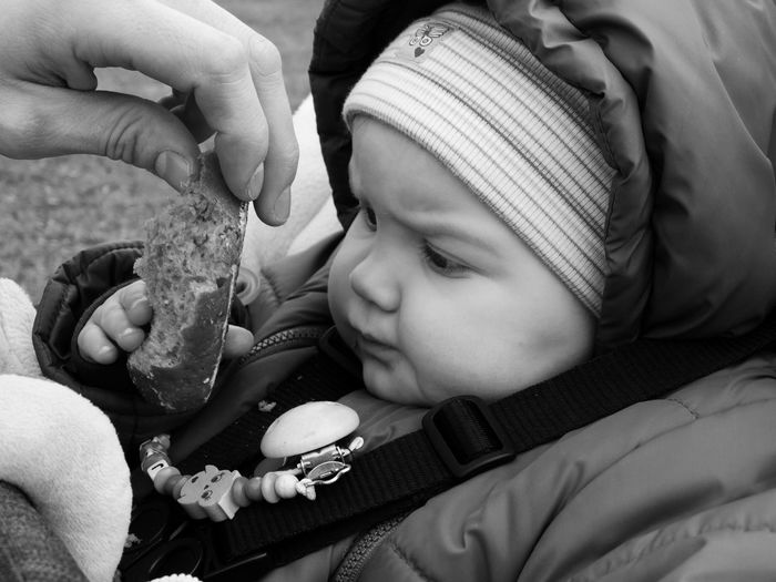 Cropped Hand Giving Bread To Baby