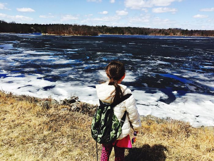 Rear View Of Girl Standing By Frozen Lake