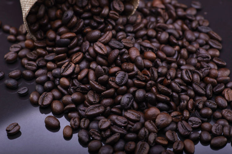 A coffee beans over the black background Coffee - Drink Roasted Coffee Bean Coffee Food And Drink Brown Large Group Of Objects Indoors  Close-up Food Freshness Still Life Abundance No People Caffeine Selective Focus Drink Roasted Pattern Focus On Foreground High Angle View