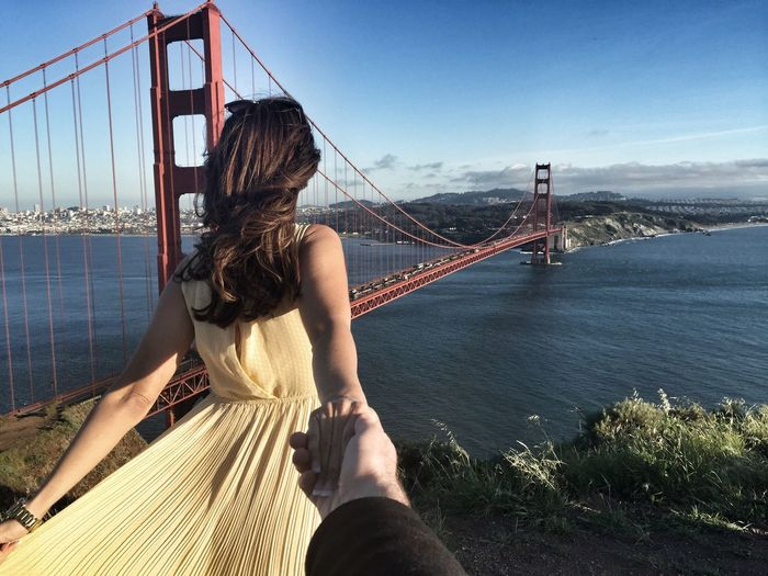 Cropped image of man hand holding woman against golden gate bridge