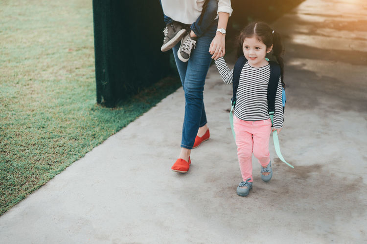 Low section of mother walking with daughter on footpath