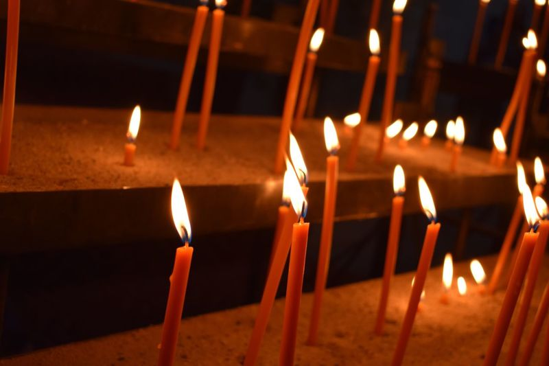 Close-up of illuminated candles on altar at church