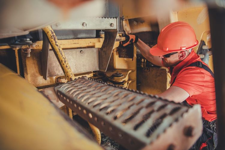 Side view of man working on machinery
