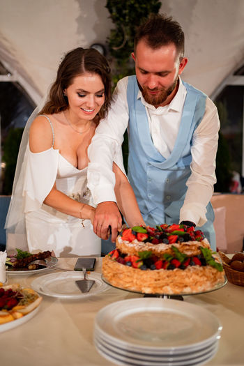 Newlywed couple cutting cake at home