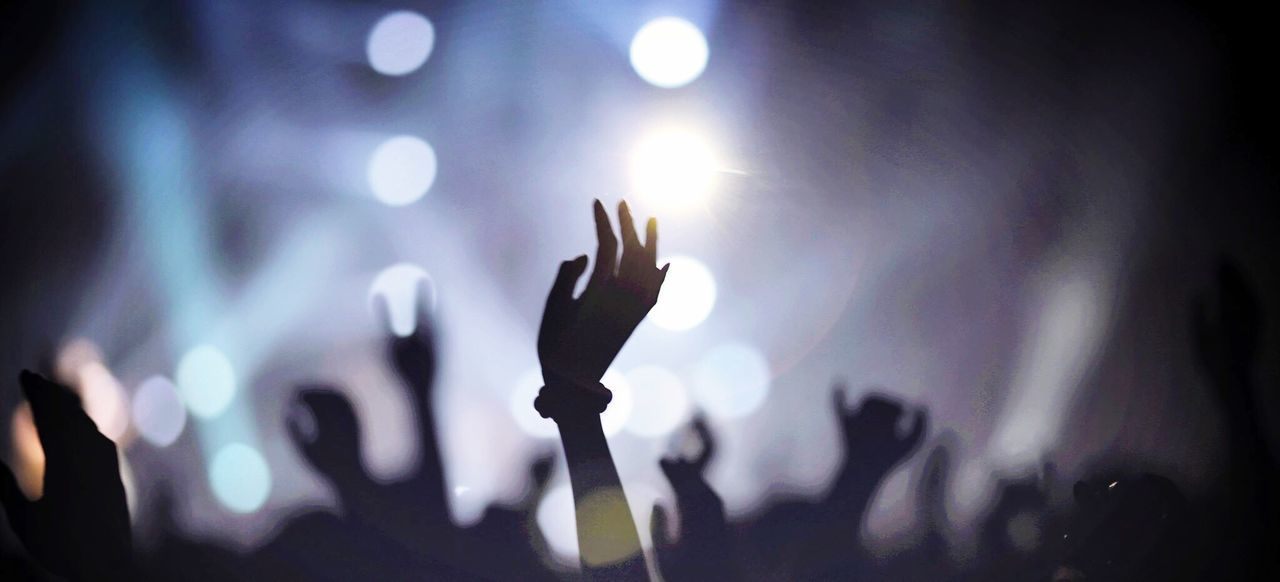 Silhouette arms raised at music concert