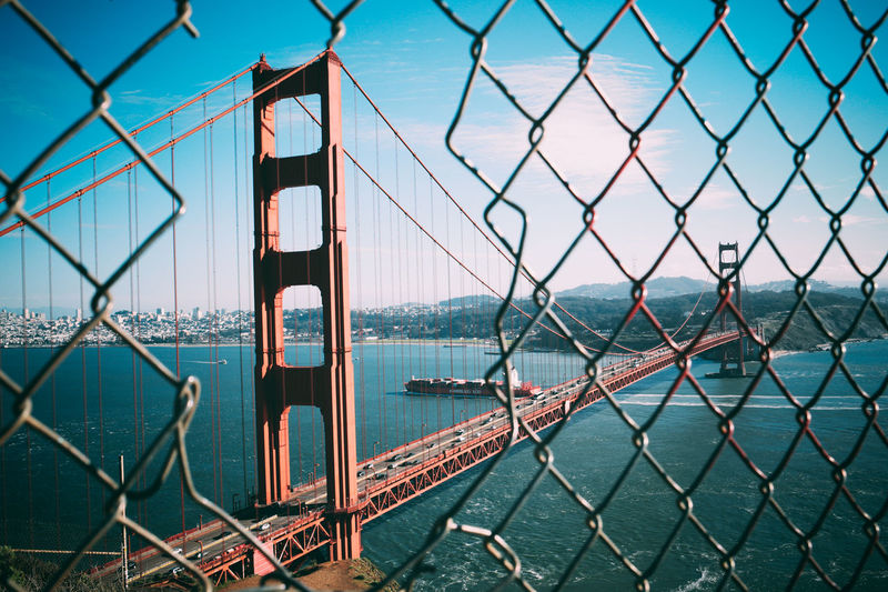 Golden gate bridge over bay against blue sky seen through chainlink fence