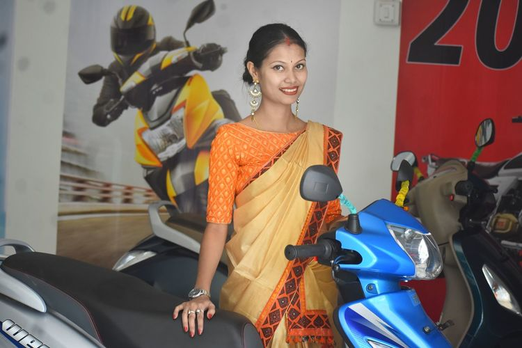 Portrait of smiling woman wearing sari standing by motorcycle