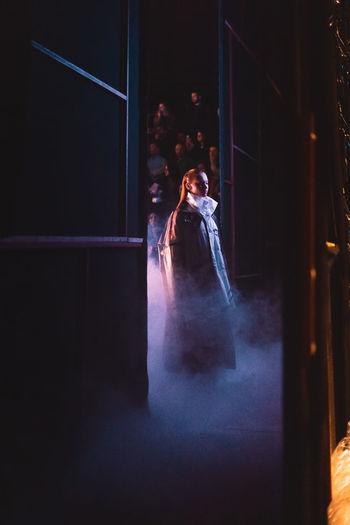 Woman standing in illuminated dark room